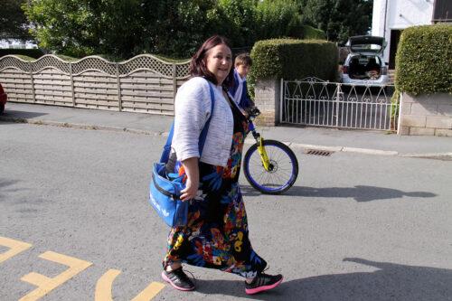 Women walking on road near school, boy on bike